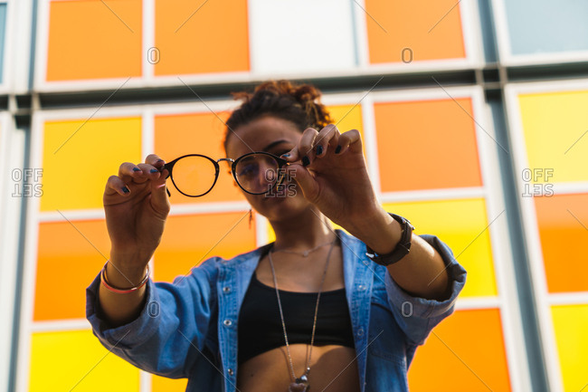 Young trendy girl holding glasses and looking at camera through them at street