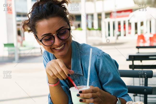 Girl laughing with a smoothie at street