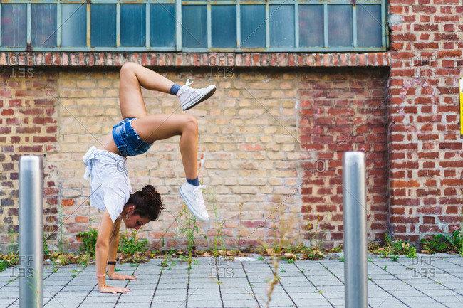 Woman in handstand at street