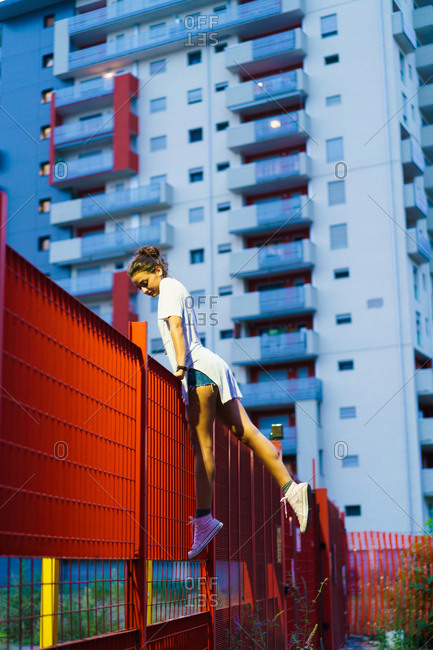 Young stylish woman balancing on metal fence in evening on background of city buildings