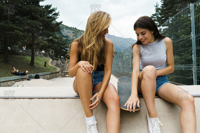 Girls posing with skateboard in park