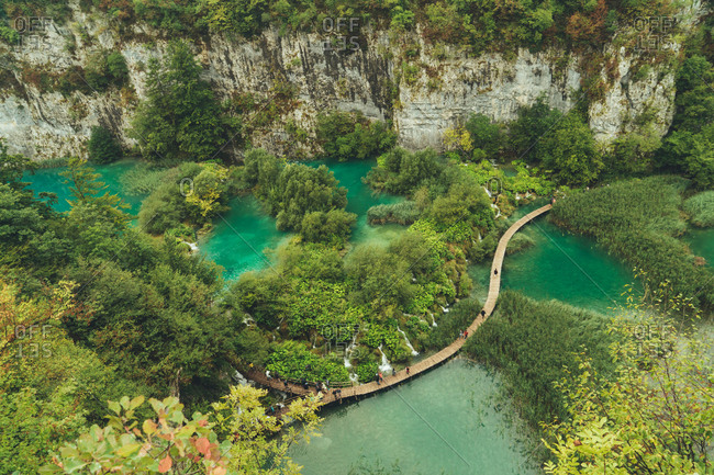 Aerial shot of beautiful green trees growing in national park with blue lakes and cliffs