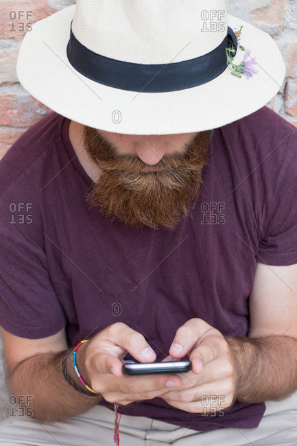 Man sitting at street with smartphone