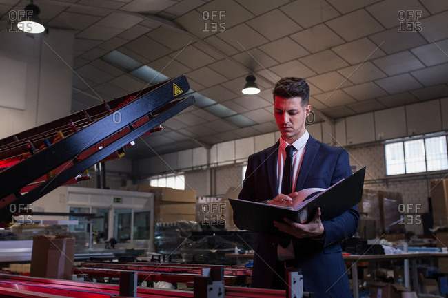 Formal man with folder checking conditions on factory inspecting workshop
