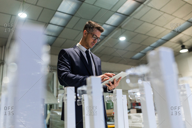 Young stylish man in elegant suit using tablet while controlling quality of factory maintenance