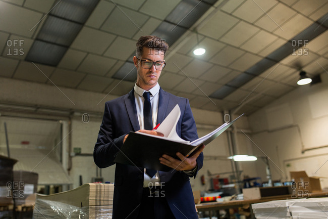 Elegant serious man standing at table in workshop of factory and reading through documents