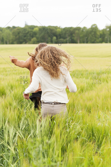 Young women running through rye field
