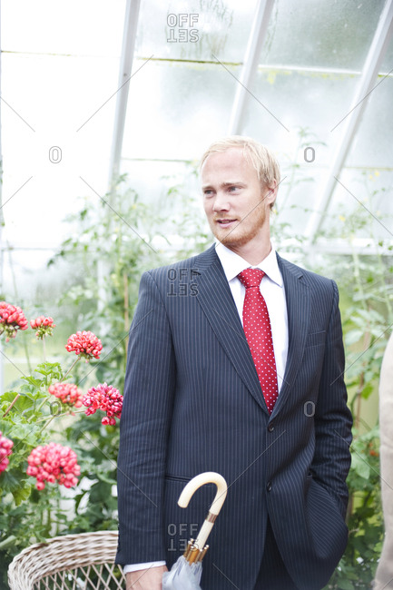 Man wearing suit in greenhouse