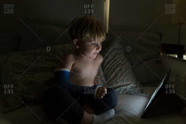 Boy with broken arm watches movie
