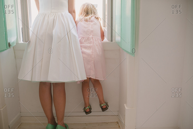 Bride and girl looking out window