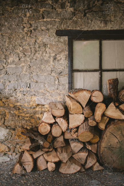 Stack of firewood by stone house