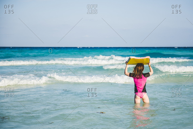 Girl with boogie board in ocean