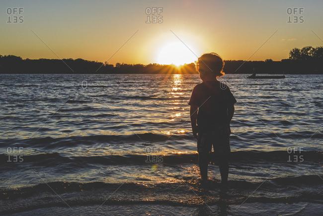 Boy wading in lake at sunset