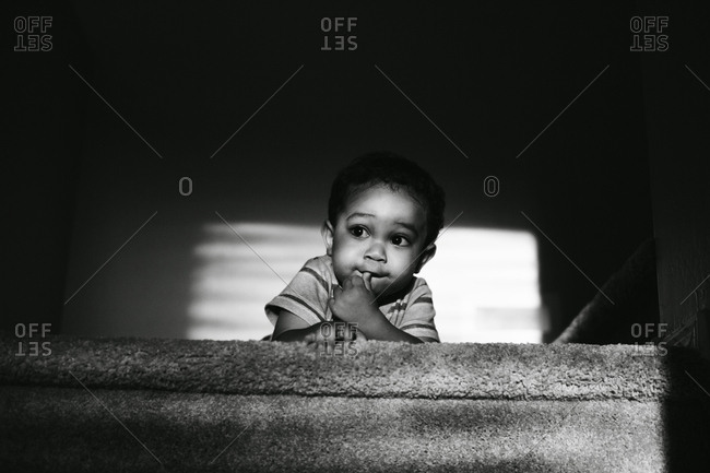 Little boy sitting at top of staircase