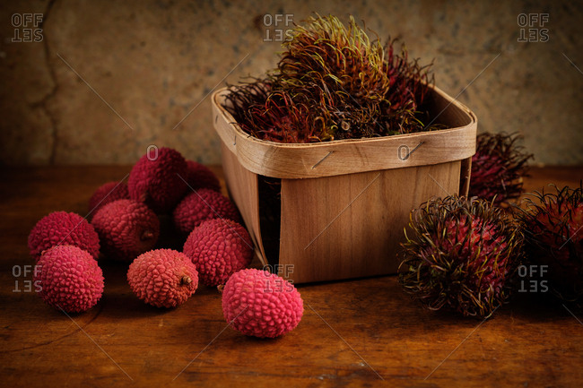 Organic lychee in basket and on wooden table
