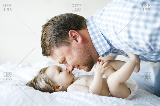 Baby girl (6-11 Months) with father face to face