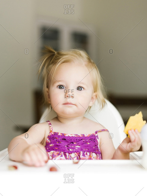 Portrait of baby girl (12-17 months) eating lunch