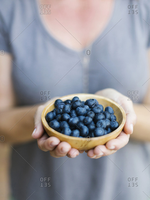 Woman holding bowl with blueberries