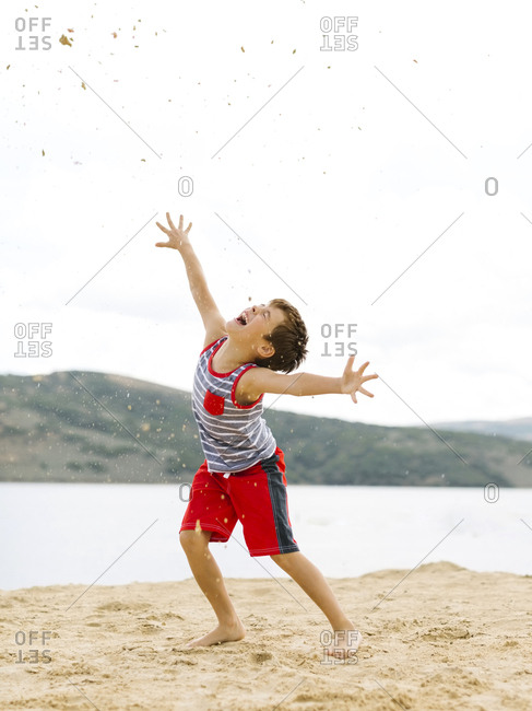 Boy (6-7) playing on beach by lake