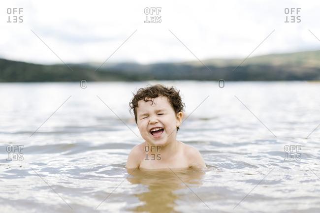 Smiling boy ( 4-5) swimming in lake