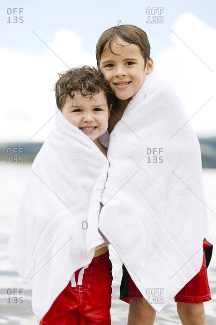 Portrait of brothers (4-5, 6-7) wrapped in towels standing by lake
