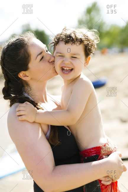 Mother kissing son (4-5) on beach