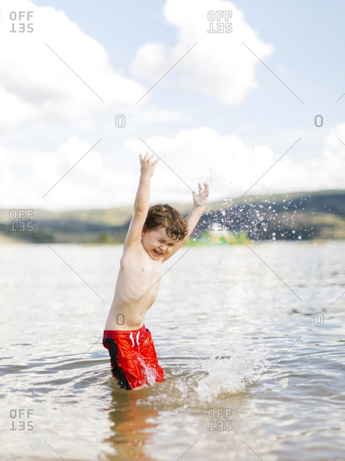 Boy (4-5) jumping in lake
