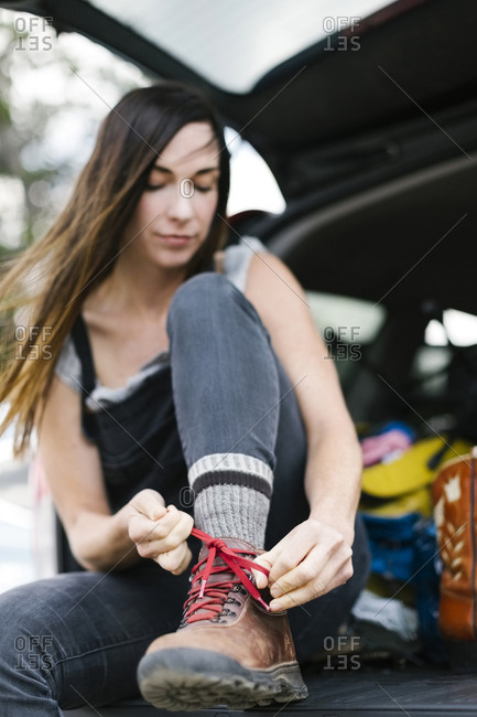 Woman sitting in car trunk and tying hiking shoes
