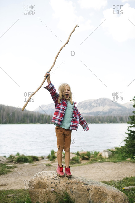 USA, Utah, Midway, Boy with stick (6-7) standing on rock by lake