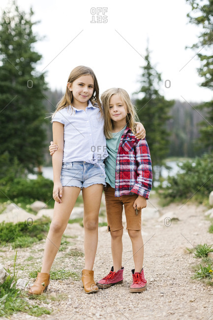 Outdoor portrait of brother (6-7) and sister ( 8-9) in forest