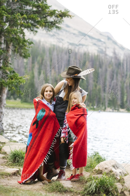 Mother with kids (6-7, 8-9) wrapped in blanket standing by lake