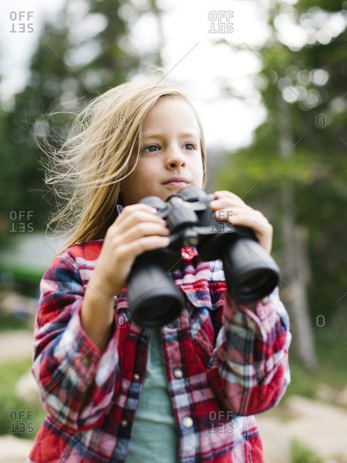 Boy (6-7) using binoculars
