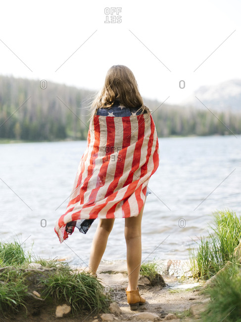USA, Utah, Midway, Rear view of girl (8-9) wrapped in us flag standing by lake
