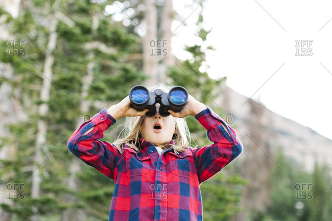 Boy (6-7) using binoculars in forest