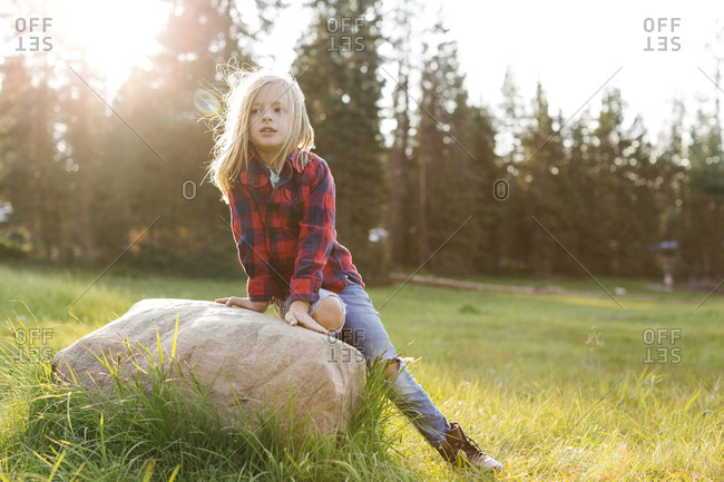 Portrait of boy (6-7) sitting on rock in forest