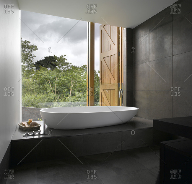 White modern spoon bath with view from open window with timber shutters