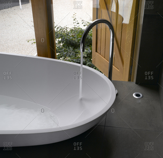 Modern egg-shaped bath and tap with running water