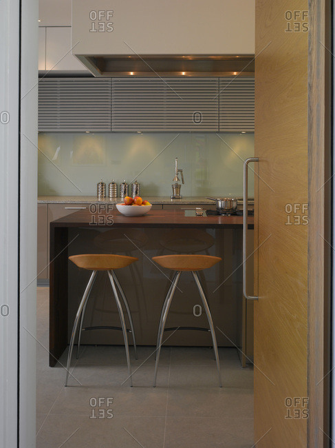 View through open pale wood modern door to kitchen with bar stools, Dulwich, London