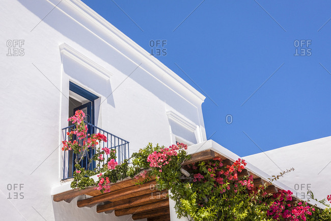 Detail of white Mediterranean house with bougainvillea covered canopy and blue sky