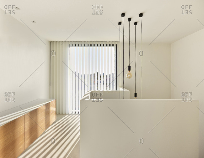 New build modern white living room with vertical blinds and shadows