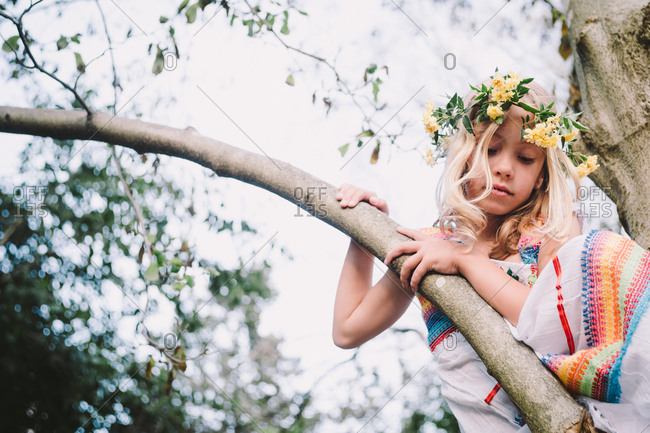 Girl wearing floral headpiece resting on the branch of a tree