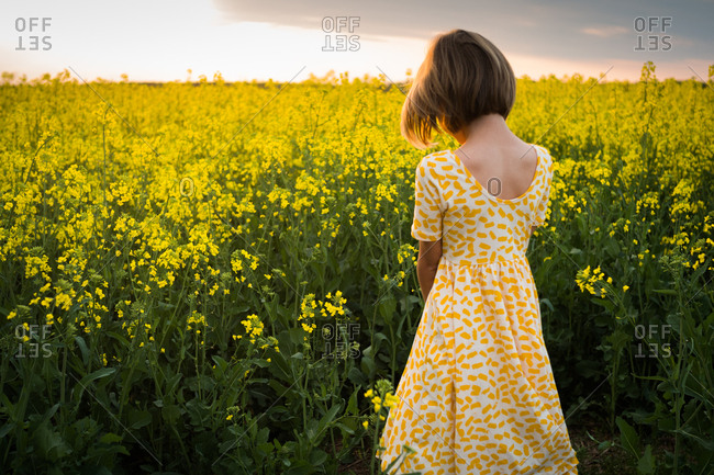 Girl wearing a yellow dress standing in a field of wildflowers
