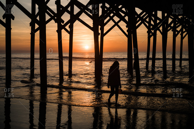 Silhouette of girl wading in the water under pier on coast at sunset