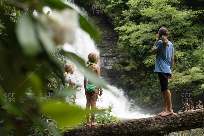 Three girls standing on log looking at waterfall