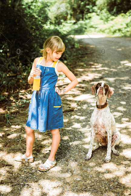 Girl wearing a blue dress looking at her pet dog