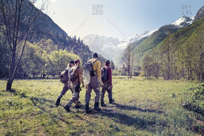 Slovenia- Bovec- four anglers walking on meadow towards Soca river