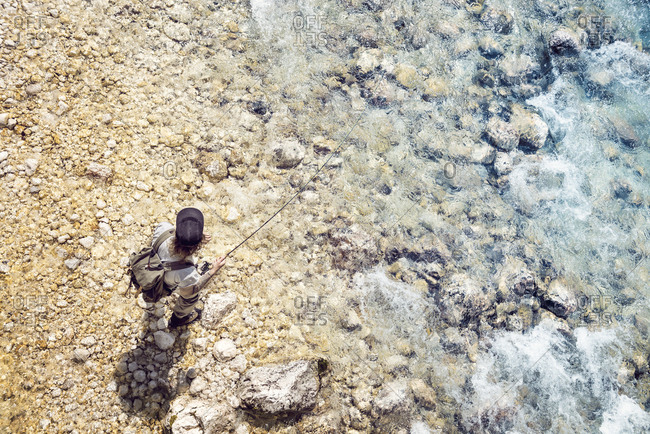 Slovenia- top view of man fly fishing in Soca river