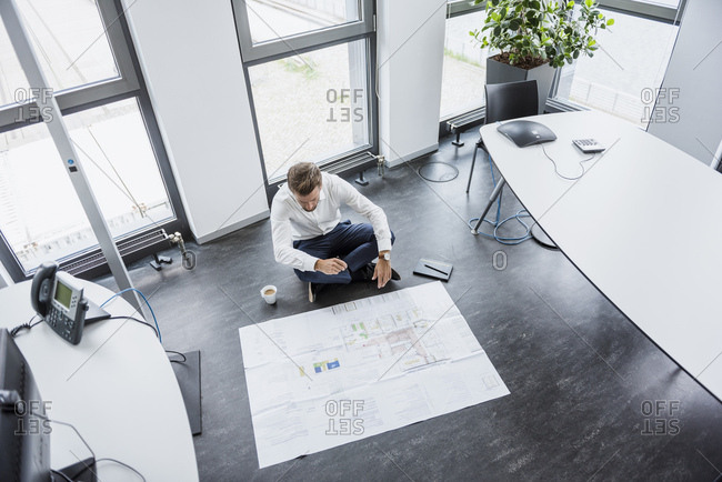 Businessman sitting on the floor of his office looking at construction plan