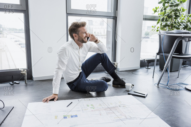 Businessman on the phone sitting on the floor of his office