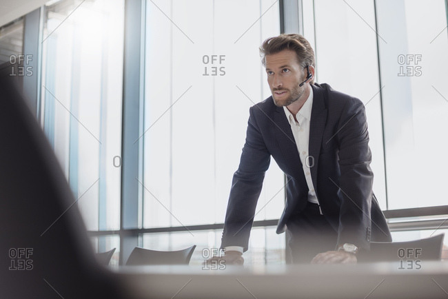 Portrait of businessman with bluetooth headset standing in conference room
